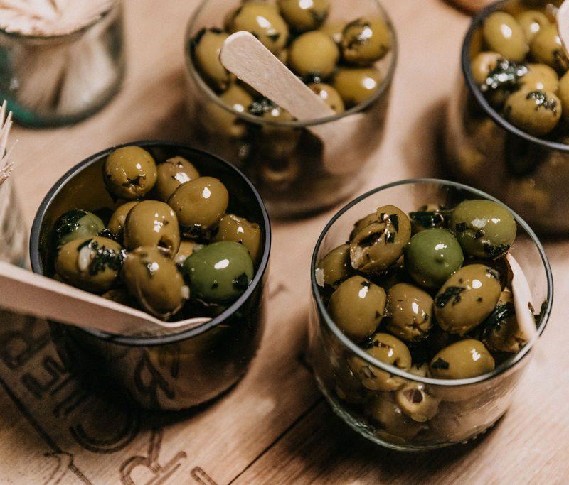 Grüne Oliven in Upcycling Gläsern auf Barriquefass